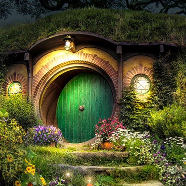 A picture of a round green door with round windows on either side embedded into the side of a hill. Flowers grow on either side of the door.